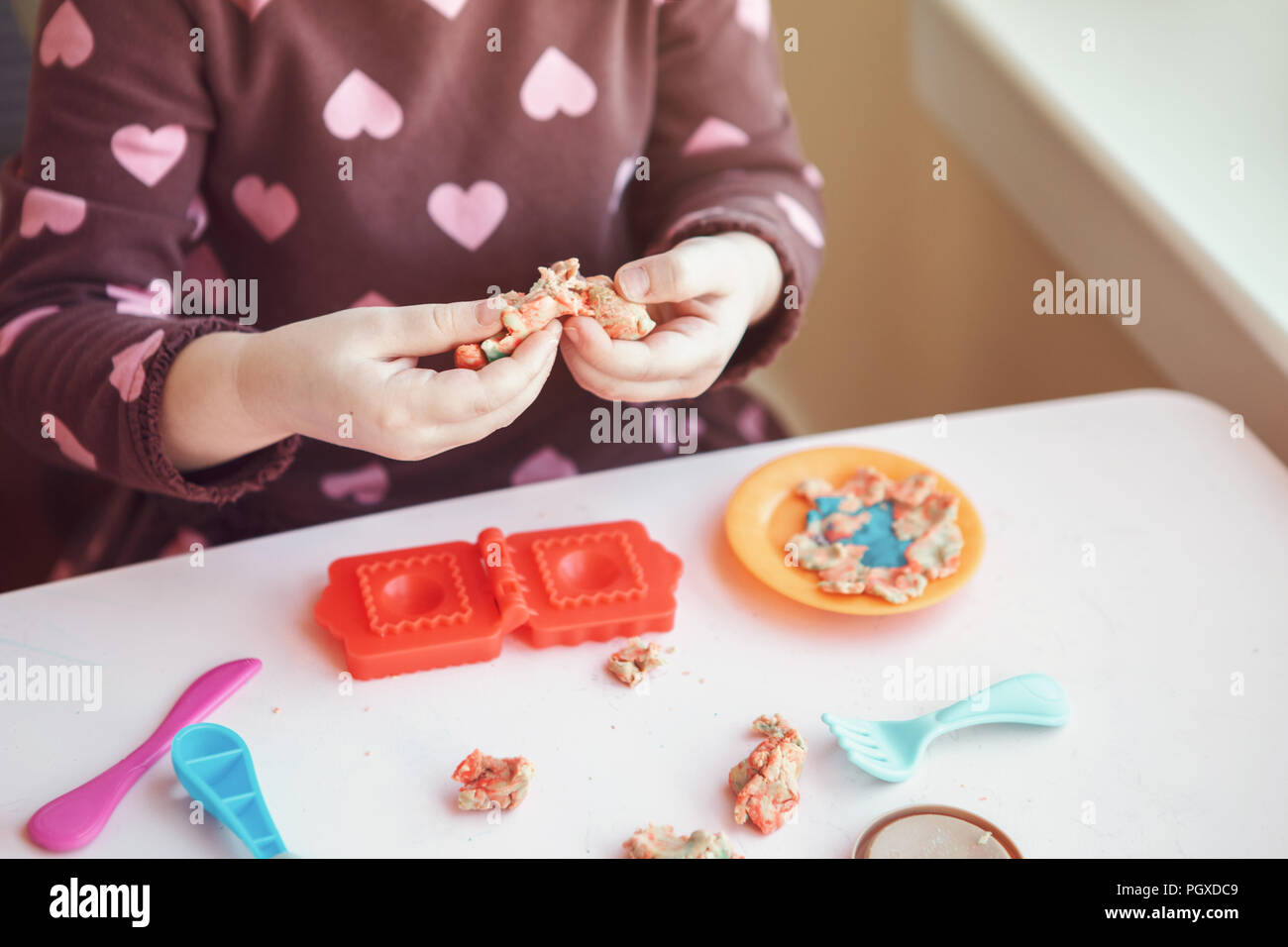 Closeup of child girl hads fingers. Kid playing plasticine playdough indoors at home. Early creativity brain development concept. Children activity. F - Stock Image