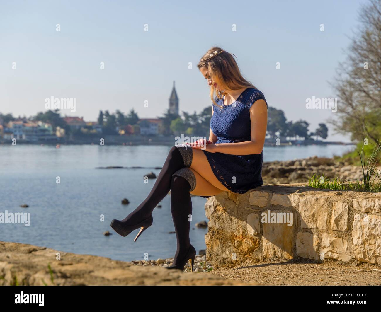 Sitting alone young woman blond hair wearing Black high heeled overknee boots - Stock Image