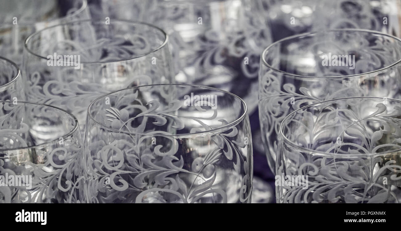 Close-up of cut and cisiliated colourless drinking glasses with abstract patterns. - Stock Image