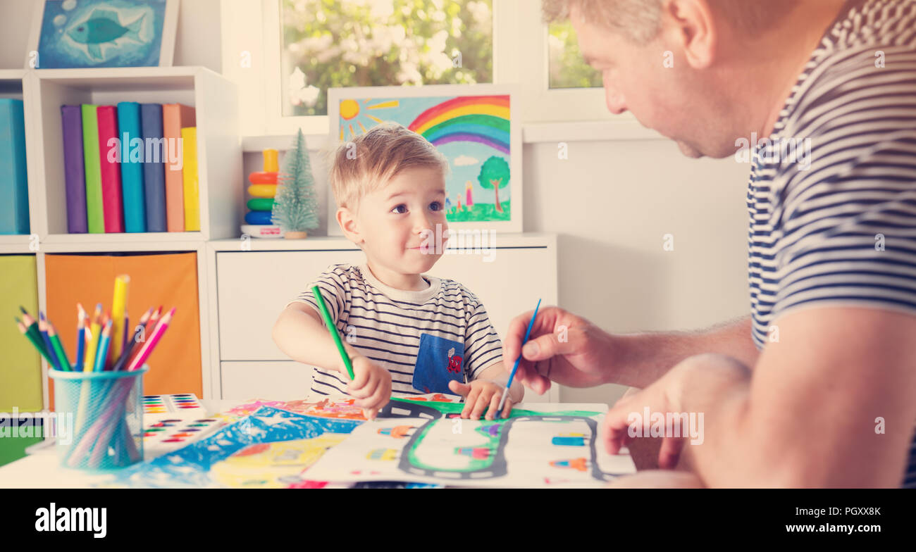 Little child drawing on the paper with father - Stock Image