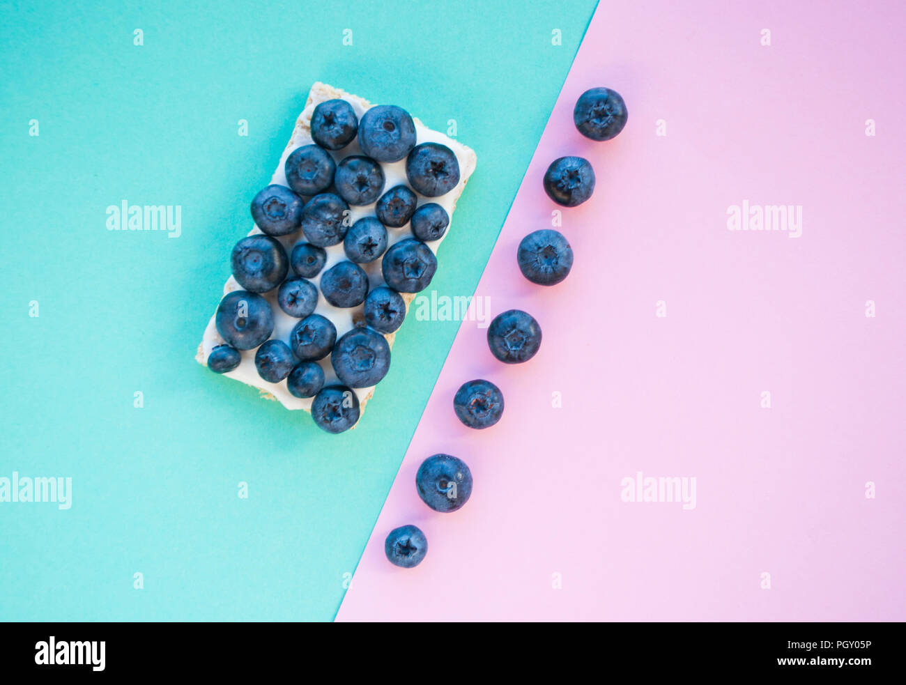 Delicious freshly picked bluberry and healthy sandwich on blue and pink background with copyspace. Healthy food concept. - Stock Image