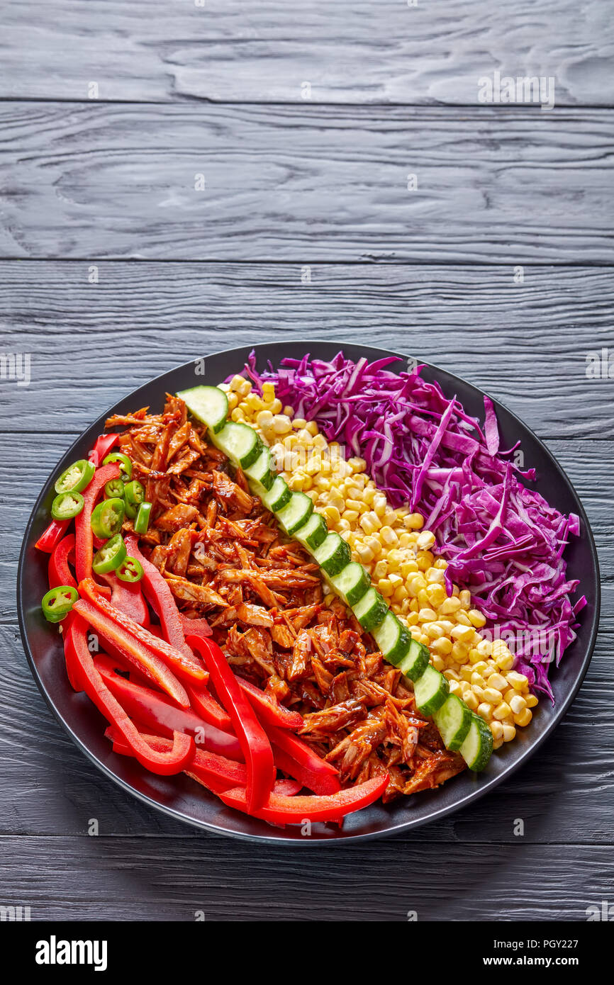 pulled pork rancho salad with coleslaw, corn, sweet pepper, cucumber and jalapeno on a black plate on a wooden table, vertical view from above - Stock Image