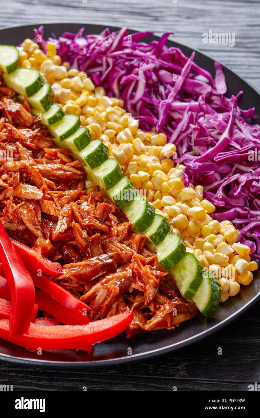 Slow cooker pulled pork rancho salad with arranged rows of thinly sliced red cabbage, corn, sweet pepper, cucumber and chopped jalapeno on a black pla - Stock Image