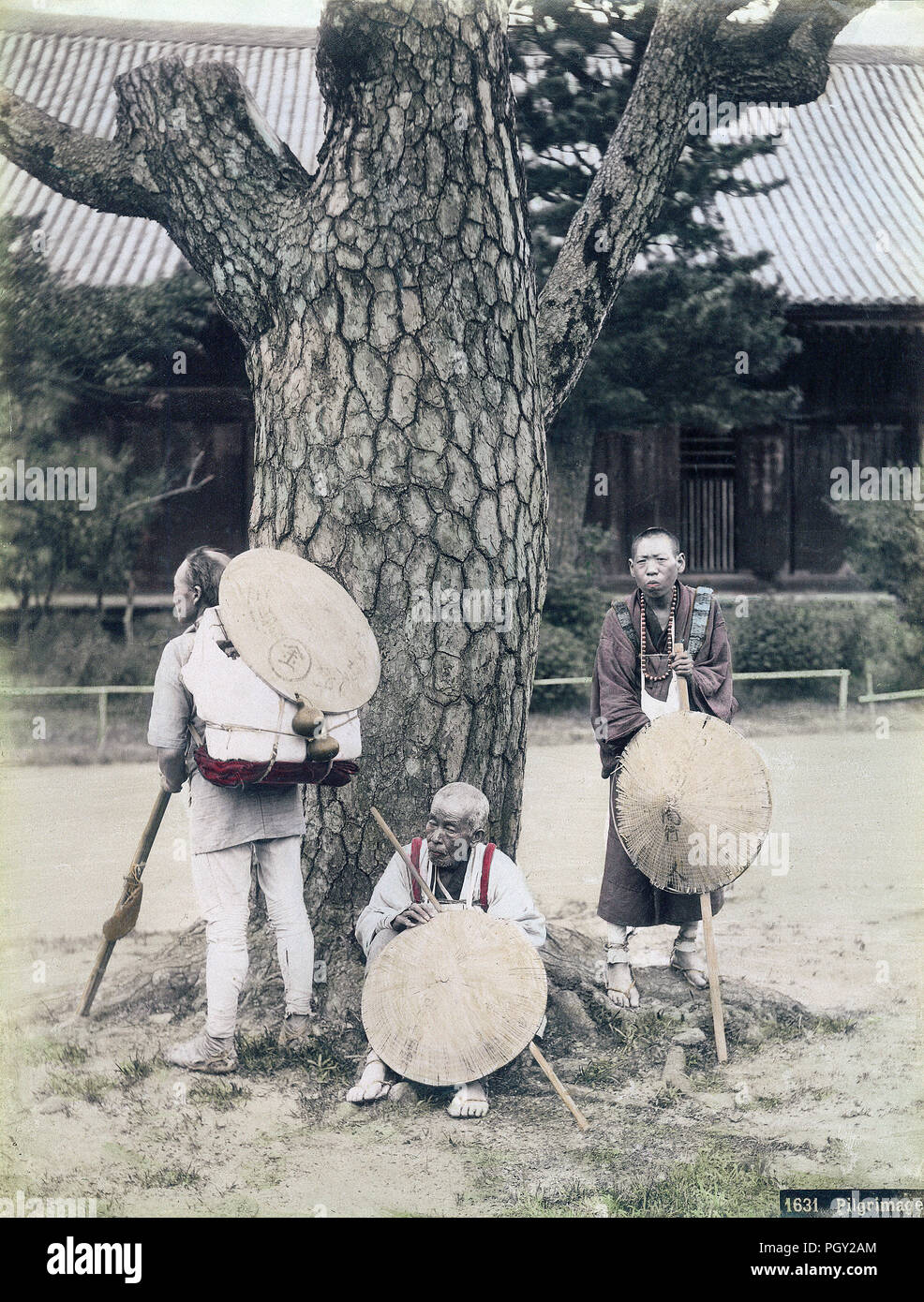 [ 1880s Japan - Buddhist Pilgrims Resting at Temple ] —   Three Pilgrims are resting at a weathered pine tree in what appears to be the grounds of a buddhist temple. They are wearing white vestments, sugegasa (sedge-woven hats) and waraji (straw sandals). They are also holding long walking sticks and carry primitive backpacks. They are on a pilgrimage to Kotohira-gu shrine, better known as Konpira-san, in Kagawa Prefecture.  19th century vintage albumen photograph. - Stock Image