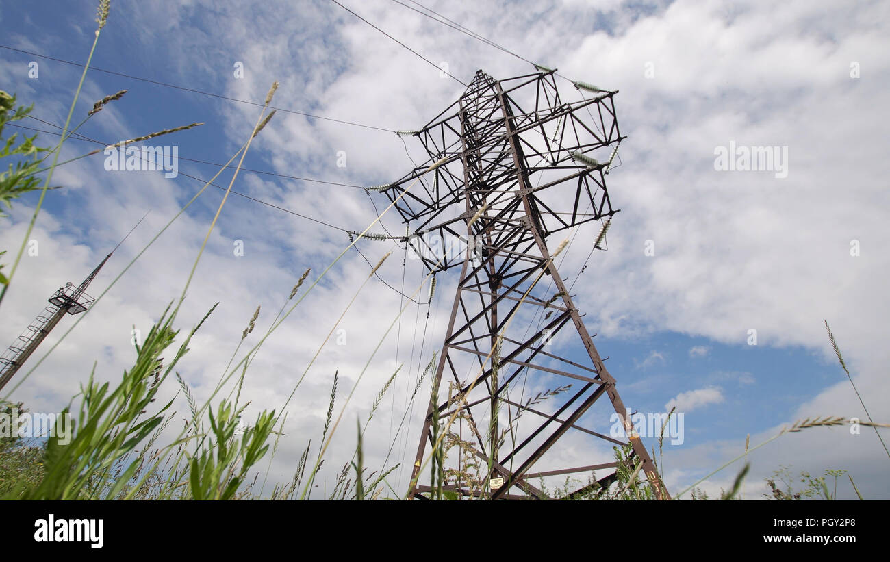High voltage post.High-voltage tower sky background. High-voltage electrical insulator electric line against the blue sky. Electricity transmission power lines. - Stock Image