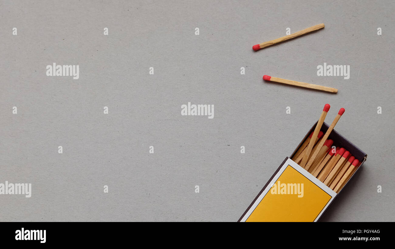 Flat lay of matches and match box on a gray background - Stock Image