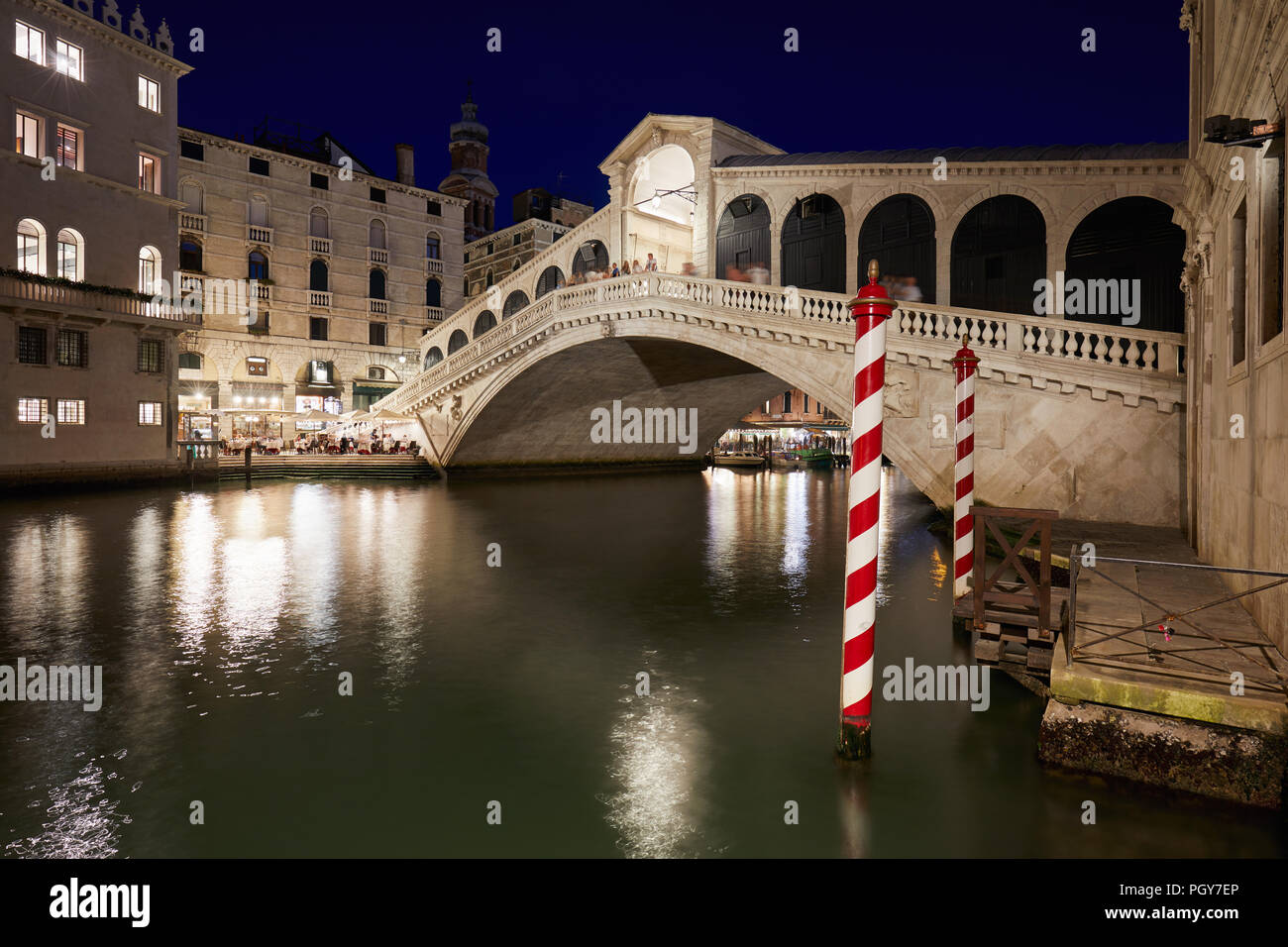 Rialto Bridge and Grand Canal with people and tourists at night in Venice, Italy - Stock Image