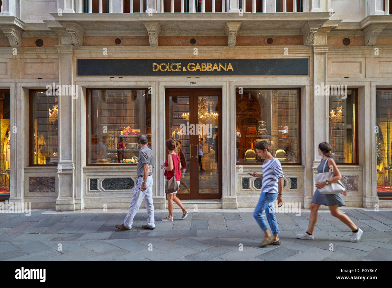 Dolce and Gabbana store with large windows and people walking in Venice, Italy - Stock Image