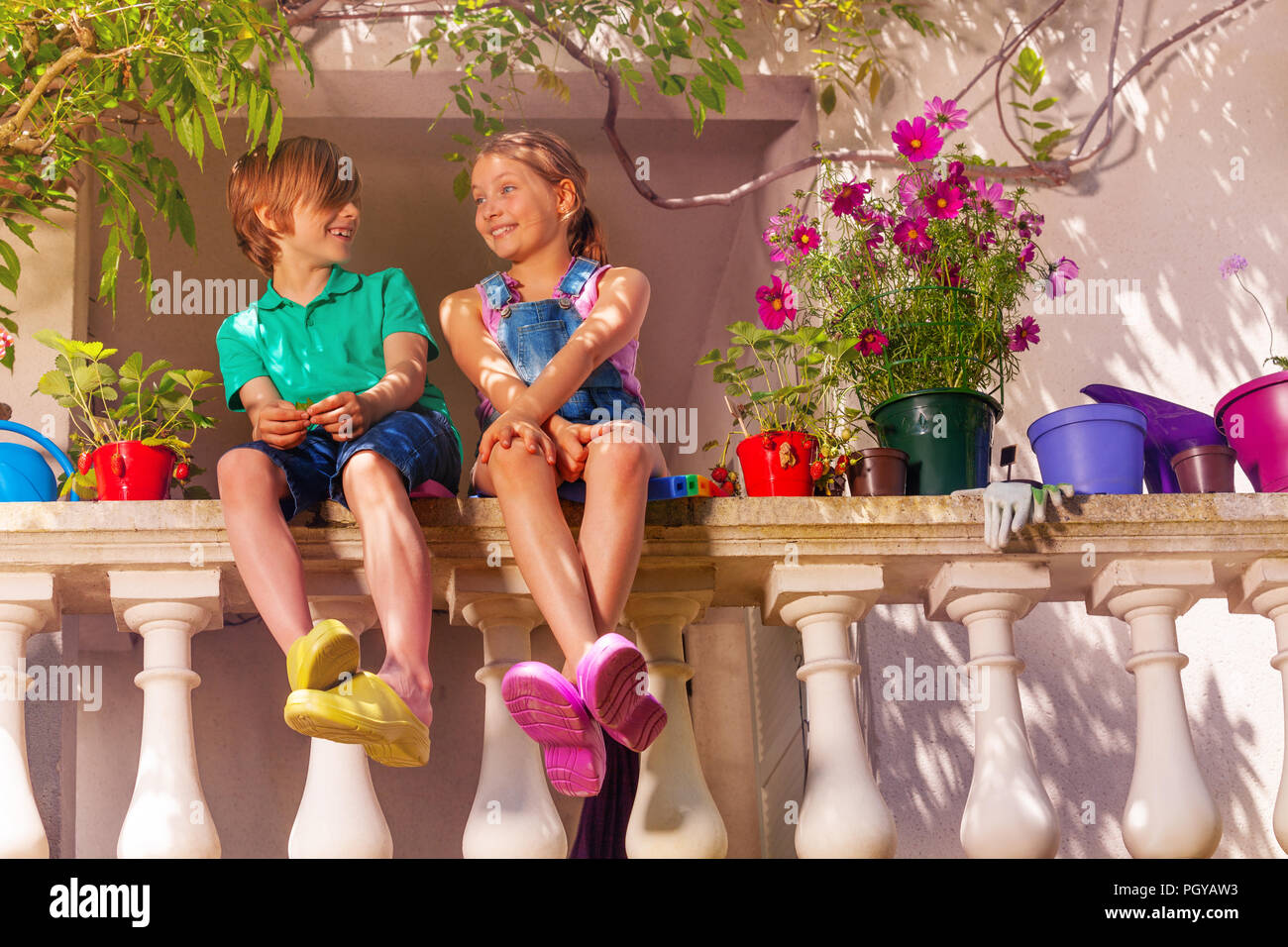 Low-angle shot of happy preteen boy and girl sitting on terrace balustrade among potted flowers - Stock Image