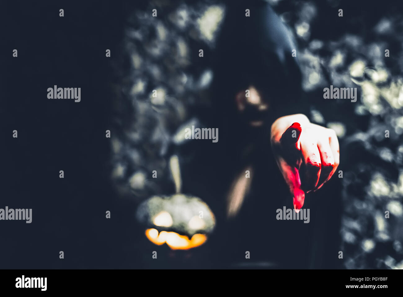 Close up of bloody wizard hand pointing to the front. Pumpkin lantern element. Horror and ghost concept. Halloween and scary movie theme. Mystery fore - Stock Image