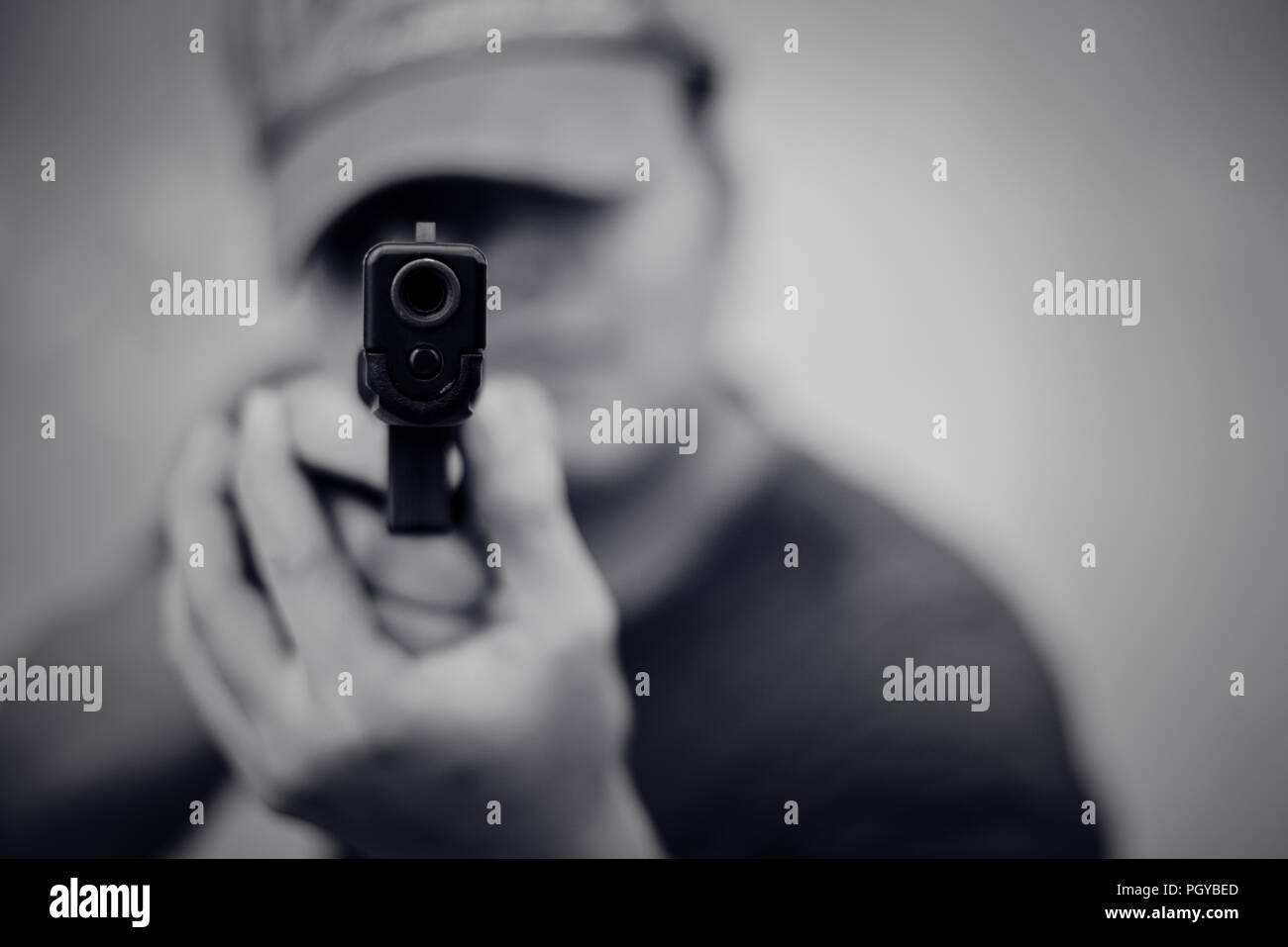 Man aiming gun and ready to shoot on front view. People and dangerous weapons concept. Criminal and security theme. Police and robber theme. Outlaw an - Stock Image