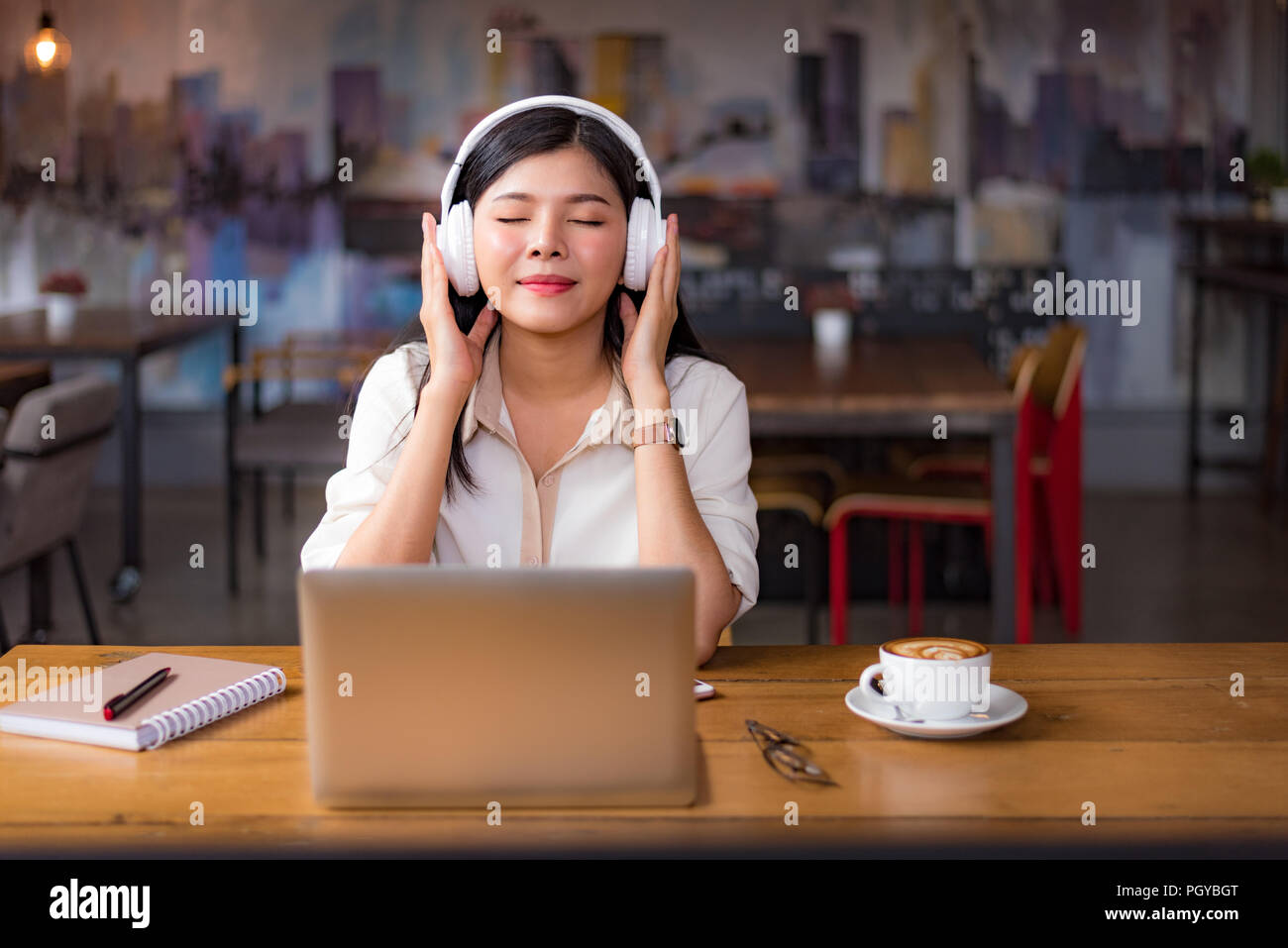 Beautiful Asian woman relaxing and listening to music in cafe with laptop computer and coffee cup. People and lifestyles concept. Freelance happy work - Stock Image