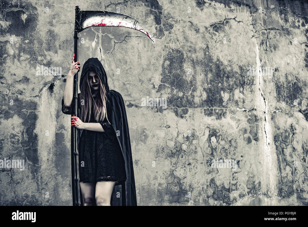 Demon witch with reaper standing in front of grunge wall background. Halloween and Religious concept. Demon angel and Satan theme. - Stock Image