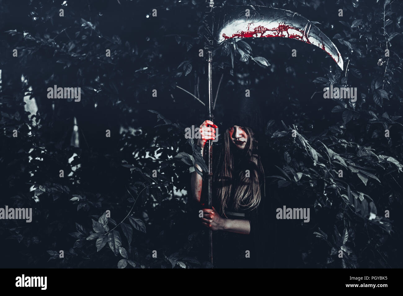 Female demon witch with bloody reaper standing in front of mystery forest background. Halloween and Religious concept. Demon angel and Satan theme. - Stock Image