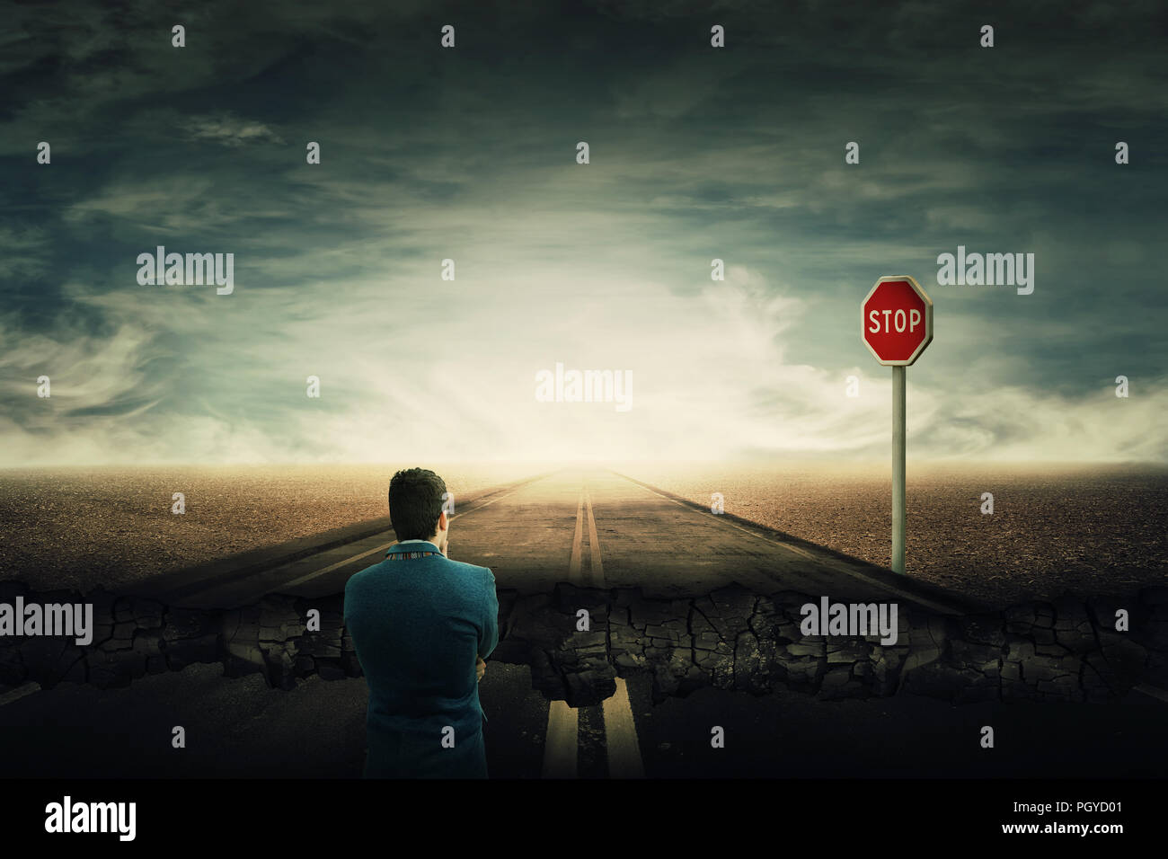 Surreal view as a man stand on a crushing asphalt road and a STOP red sign in front. Deep hole in the ground, chasm as broken way for businessman. Car - Stock Image