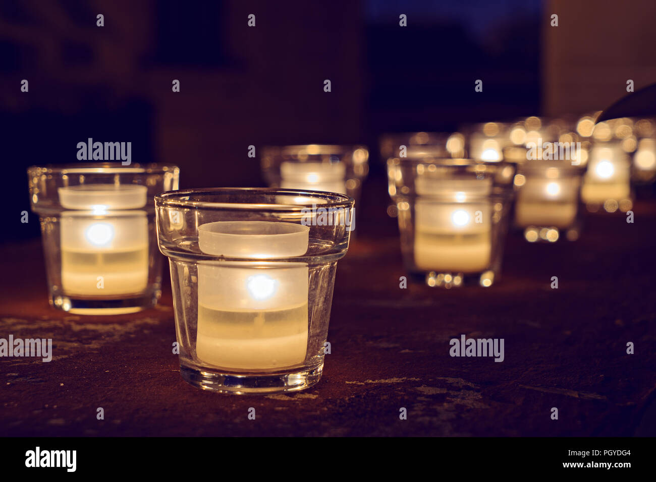 Large group of glass jars with burning candles on the dark background, selective focus. Hygge concept - Stock Image