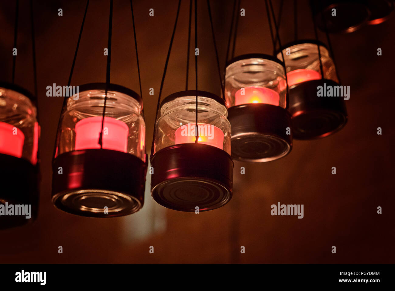 Hanging candlesticks jars with burning candles. Cozy and hygge concept - Stock Image