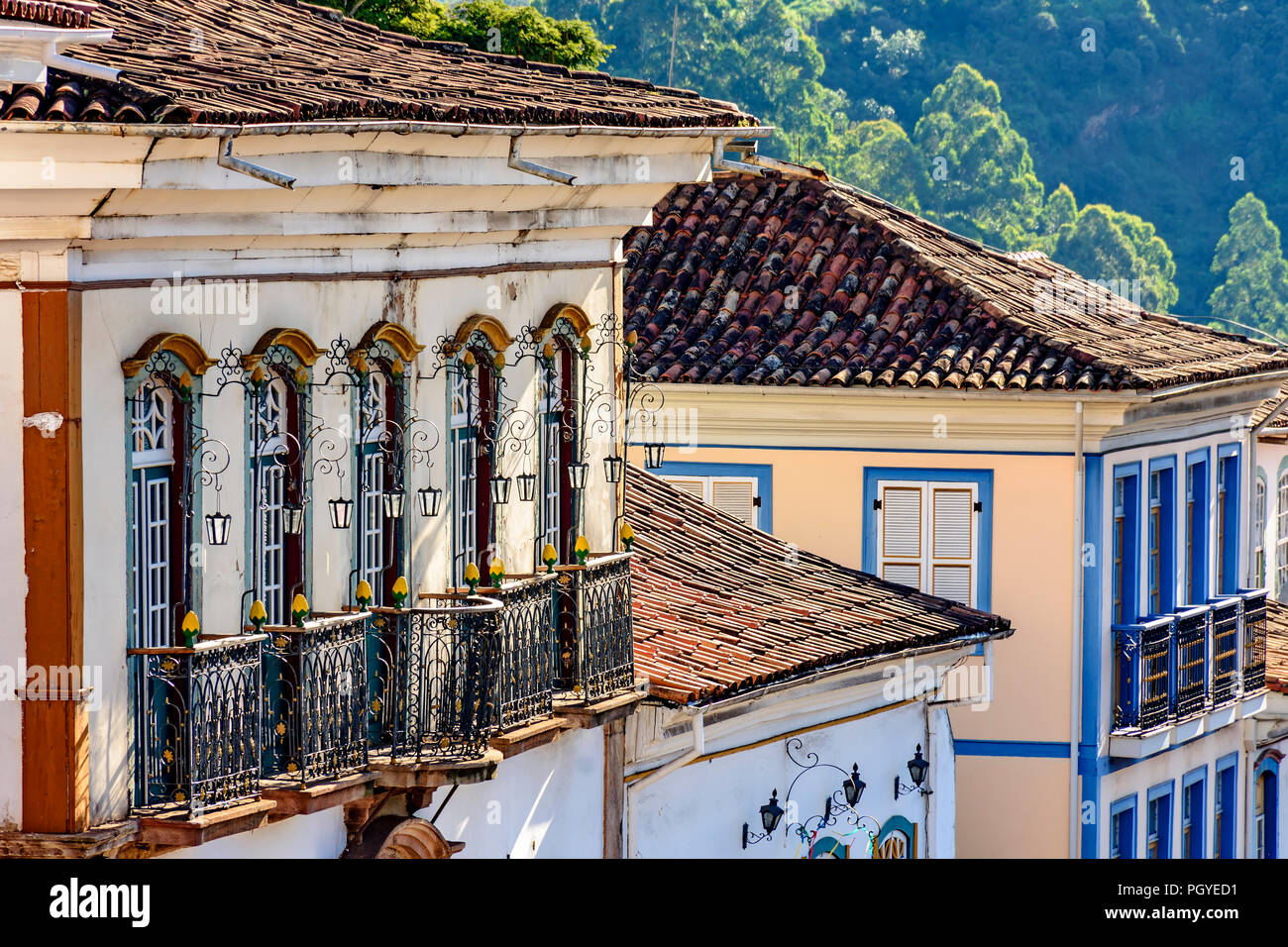 Facade of old and historical houses built in colonial architecture with their balconies, roofs and colorful details in the historical city of Ouro Pre - Stock Image