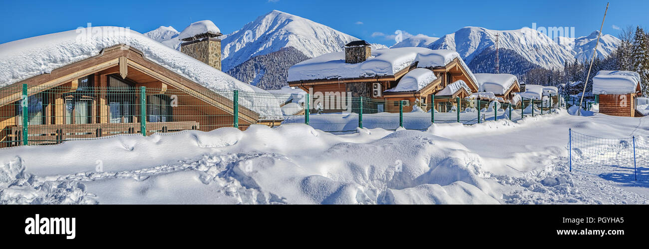RED GLADE, SOCHI, RUSSIA - JANUARY 31, 2016: Snow-covered cottages against the backdrop of the mountains. Mountain resort 'Laura, GAZPROM' - Stock Image