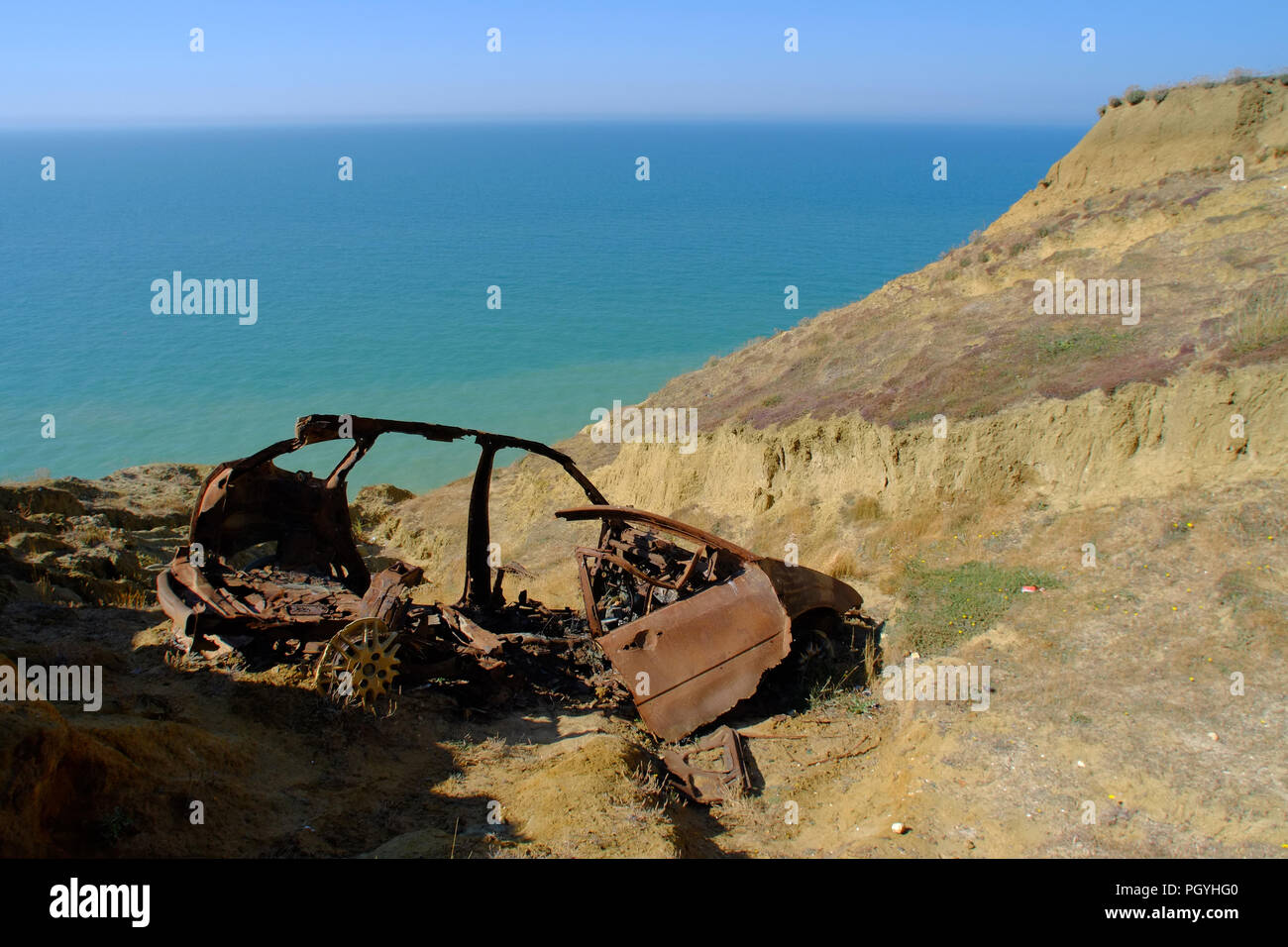 Wreck of a burned out car on the chalk cliffs above the sea near Newhaven, East Sussex, UK - Stock Image