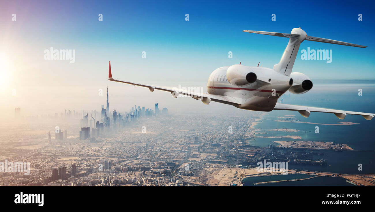 Luxury private jetliner flying above Dubai city, UAE. Modern and fastest mode of transportation, symbol of luxury and business traveling. - Stock Image