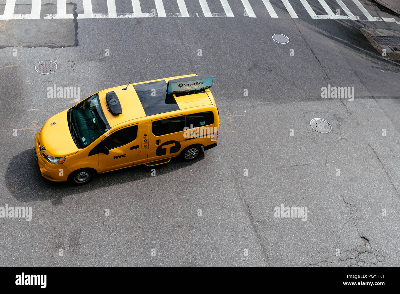 New York City, USA - June 22, 2018: Yellow taxi cab in Manhattan. High angle view. Nissan NV200 is the model of the New York City taxi - Stock Image
