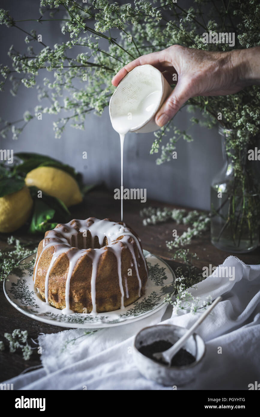 Crop view of hand holding cup of sweet dressing and pouring on delicious pie placed on dish near cup of poppy seed and flowers in vase - Stock Image