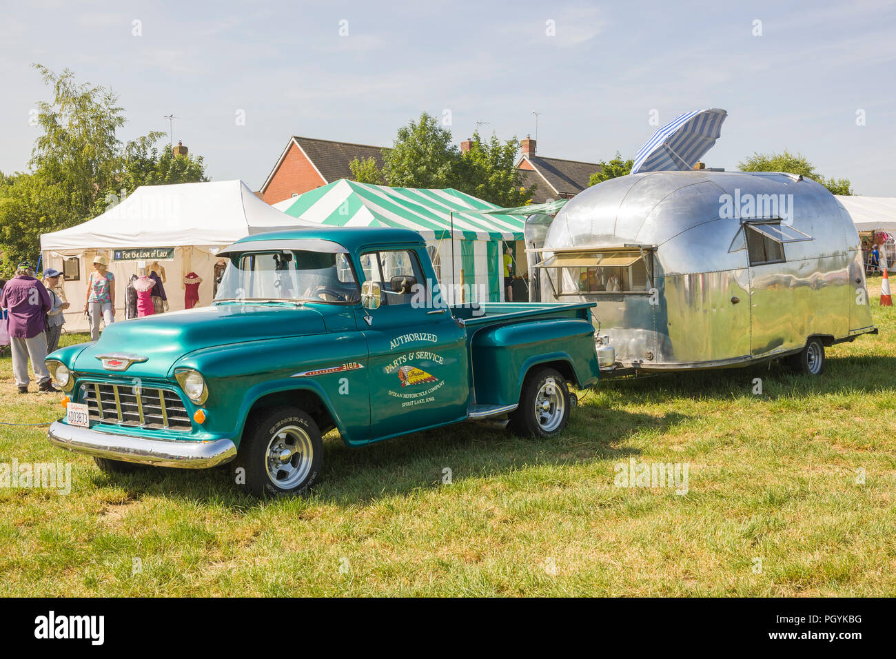 An old American Airstream streamlined caravan at Heddington Country Fair and Steam show in Wiltshire England UK towed by an old Chevrolet 3100 America - Stock Image