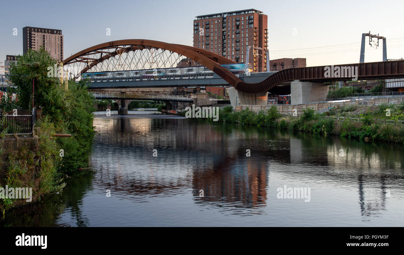 A TransPennine Express train crosses the River Irwell between Manchester and Salford on the newly constructed Ordsall Chord railway, part of the 'Nort - Stock Image
