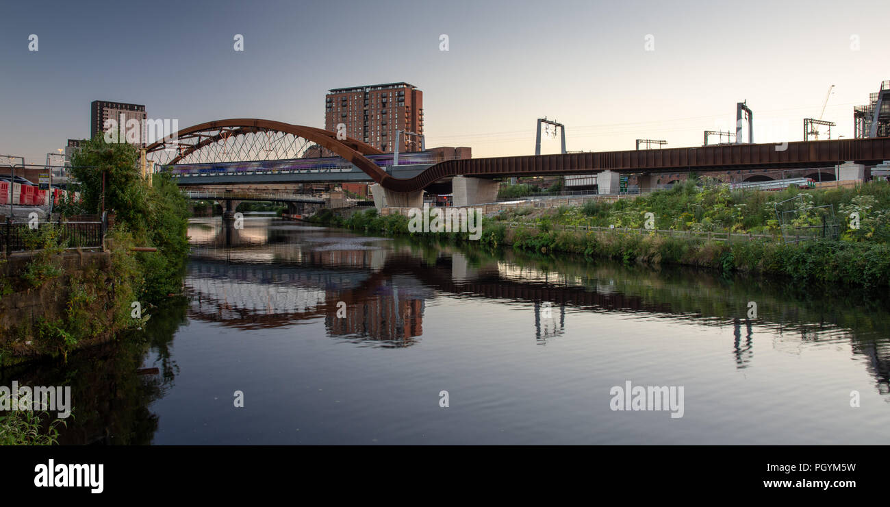 A Northern Rail train crosses the River Irwell between Manchester and Salford on the newly constructed Ordsall Chord railway, part of the 'Northern Po - Stock Image