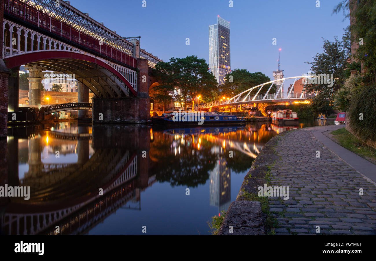 Manchester, England, UK - June 30, 2018: Houseboats light up in Castlefield Basin as dusk falls on Manchester City Centre, with a Metrolink tram passi - Stock Image
