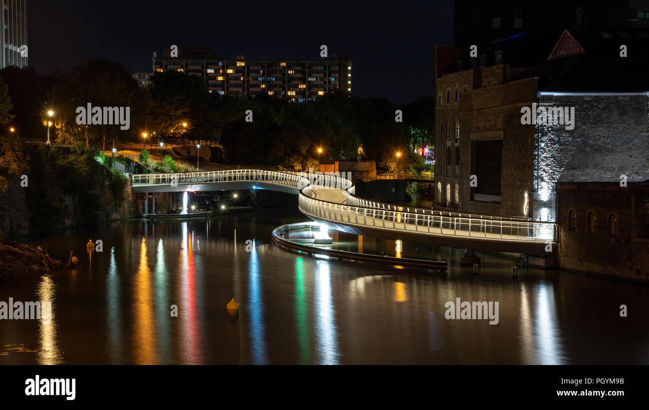 Bristol, England, UK - August 9, 2018: The modern Castle Bridge footbridge snakes across Bristol's Floating Harbour at Finzel's Reach. - Stock Image