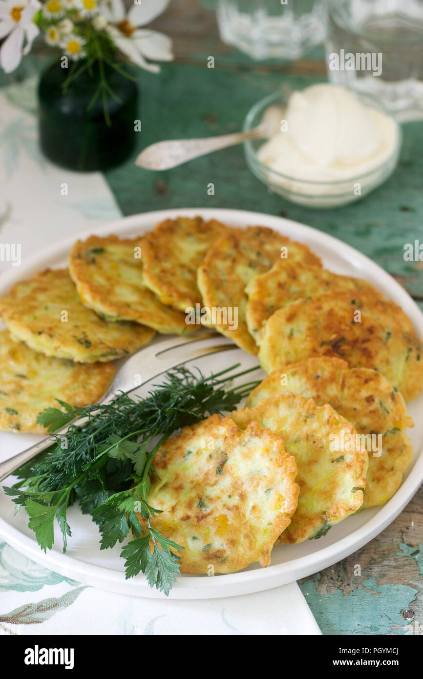 Pancakes with zucchini and sweet corn, served with sour cream, parsley and dill. Vegetarian food. - Stock Image