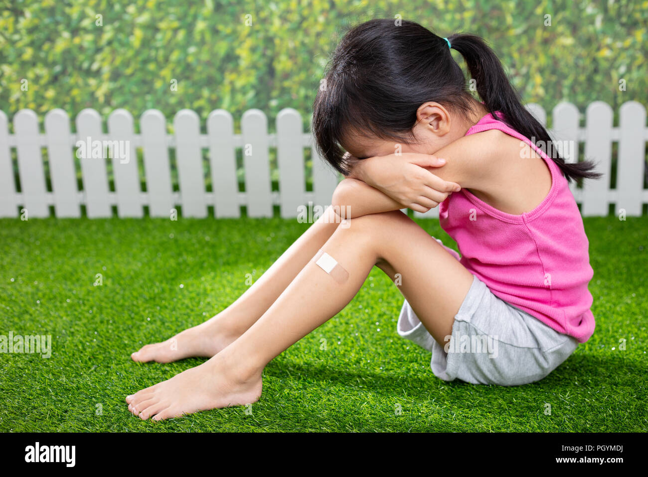 Asian Little Chinese girl sitting on the grass and crying at outdoor park - Stock Image