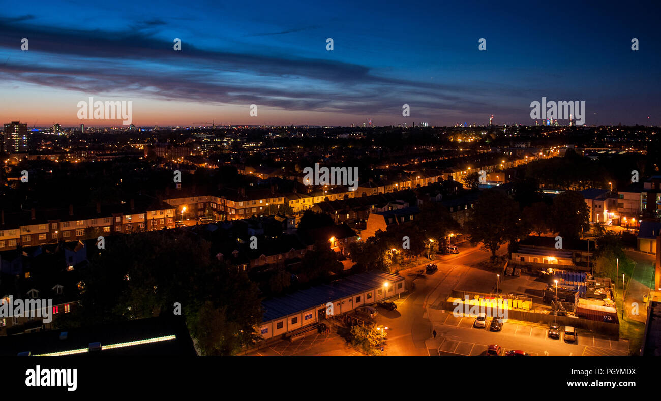 London, England, UK - June 3, 2013: The sun sets over the suburban cityscape of Tooting, with the skyscrapers of the skyline of London in the distance - Stock Image