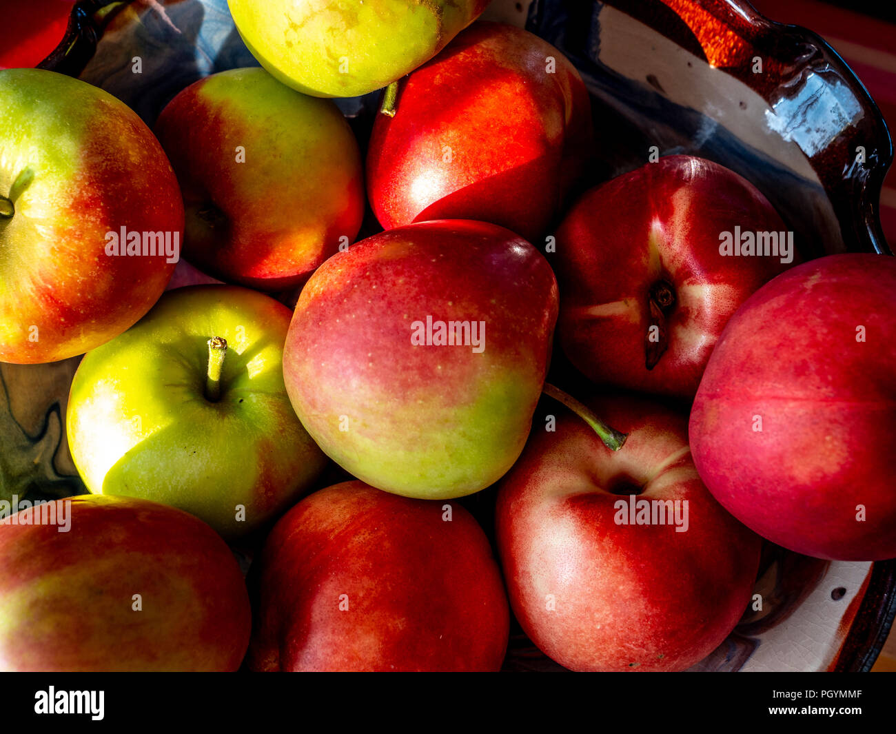 group of red fresh swiss apples in a bowl with sun shade on it - Stock Image
