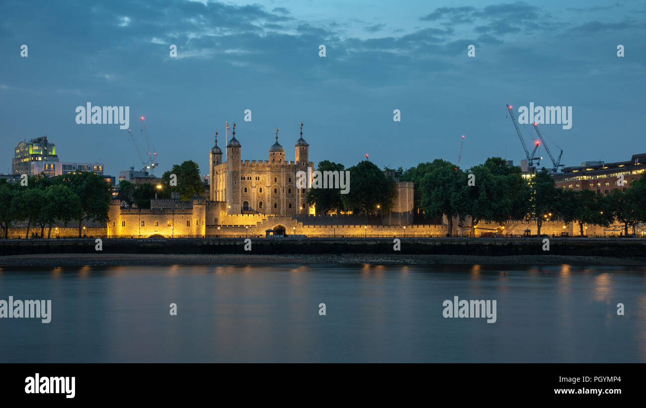 London, England, UK - June 1, 2018: The mediaeval castle keep or the Tower of London is lit up at night beside the River Thames. - Stock Image