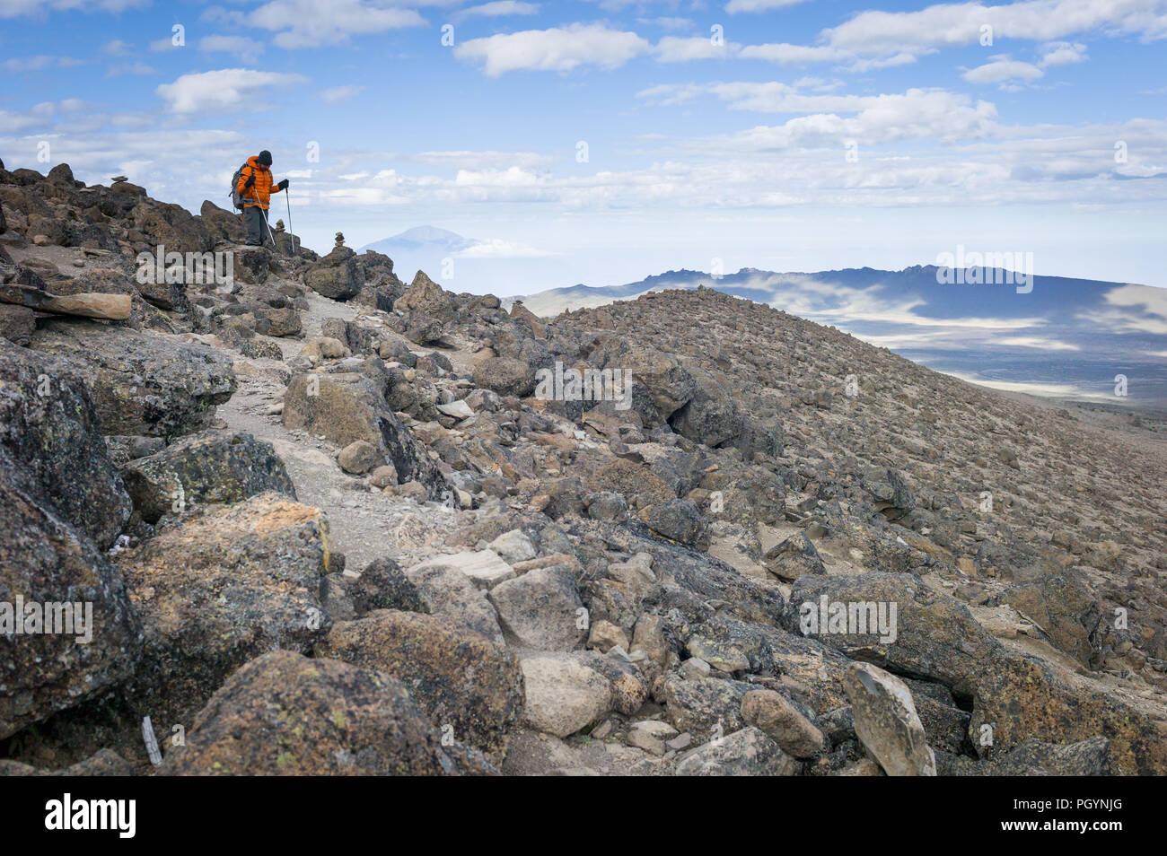 Hiker on northern circuit, with Mount Meru in the background, Mount Kilimanjaro, Kilimanjaro Region, Tanzania. - Stock Image