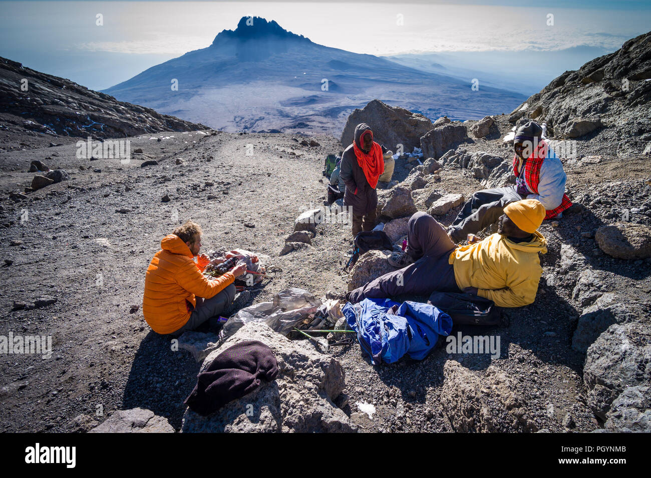 Hikers resting after leaving Uhuru peak summit of Kibo, Mount Kilimanjaro, Kilimanjaro Region, Tanzania. - Stock Image