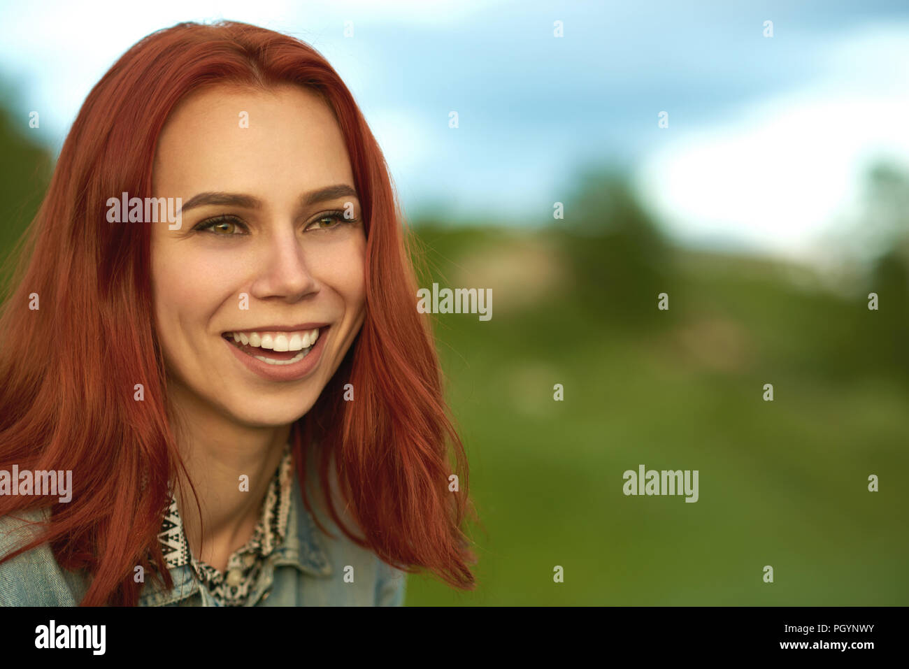 Laughing woman with short red hair posing on green field