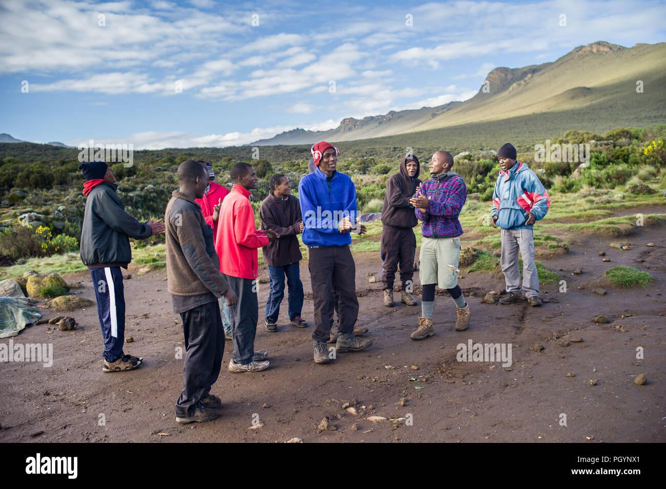Porters, guides and cooks sing in Shira 1 Camp, Shira Plateau, Mount Kilimanjaro, Kilimanjaro Region, Tanzania. - Stock Image