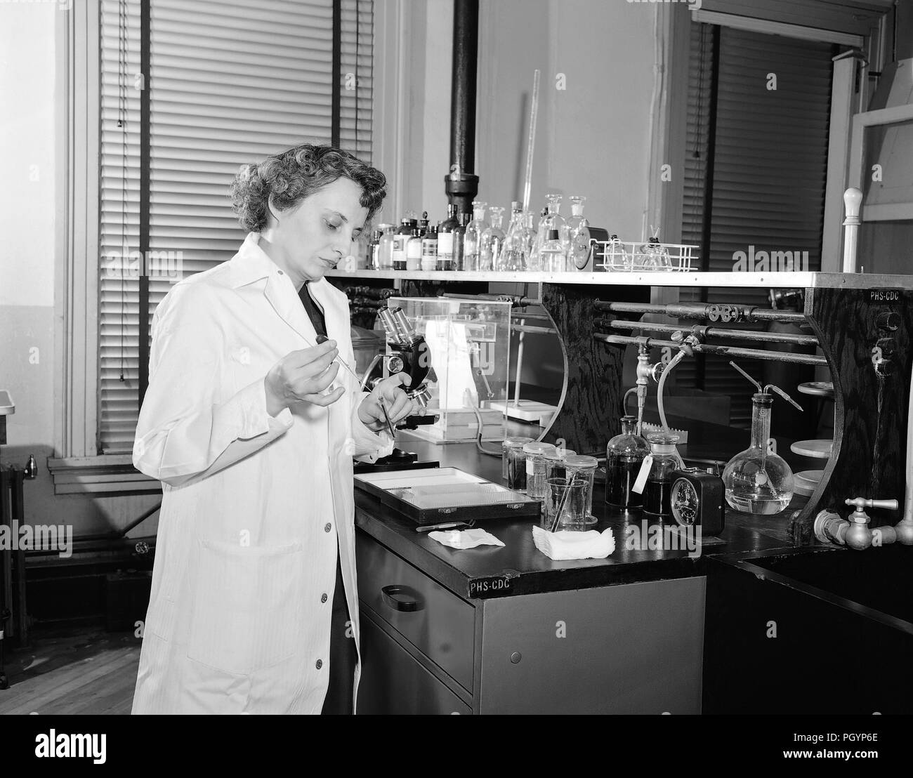 Black and white photograph of Dr Marguerite Candler, wearing a white coat while performing an experimental analysis in the Centers for Disease Control's experimental hematology laboratory, with various scientific apparatus visible in the background, image courtesy CDC, 1955. () - Stock Image