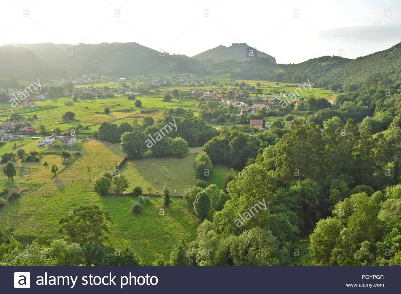 Green Spain - lush pastures with rural dwellings and hills of Cantabria in Northern Spain. - Stock Image