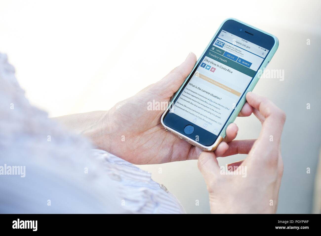 Woman reading about Zika virus in Costa Rica on her smartphone, 2016. Image courtesy Centers for Disease Control (CDC) / National Center for Emerging and Zoonotic Infectious Diseases (NCEZID). () - Stock Image