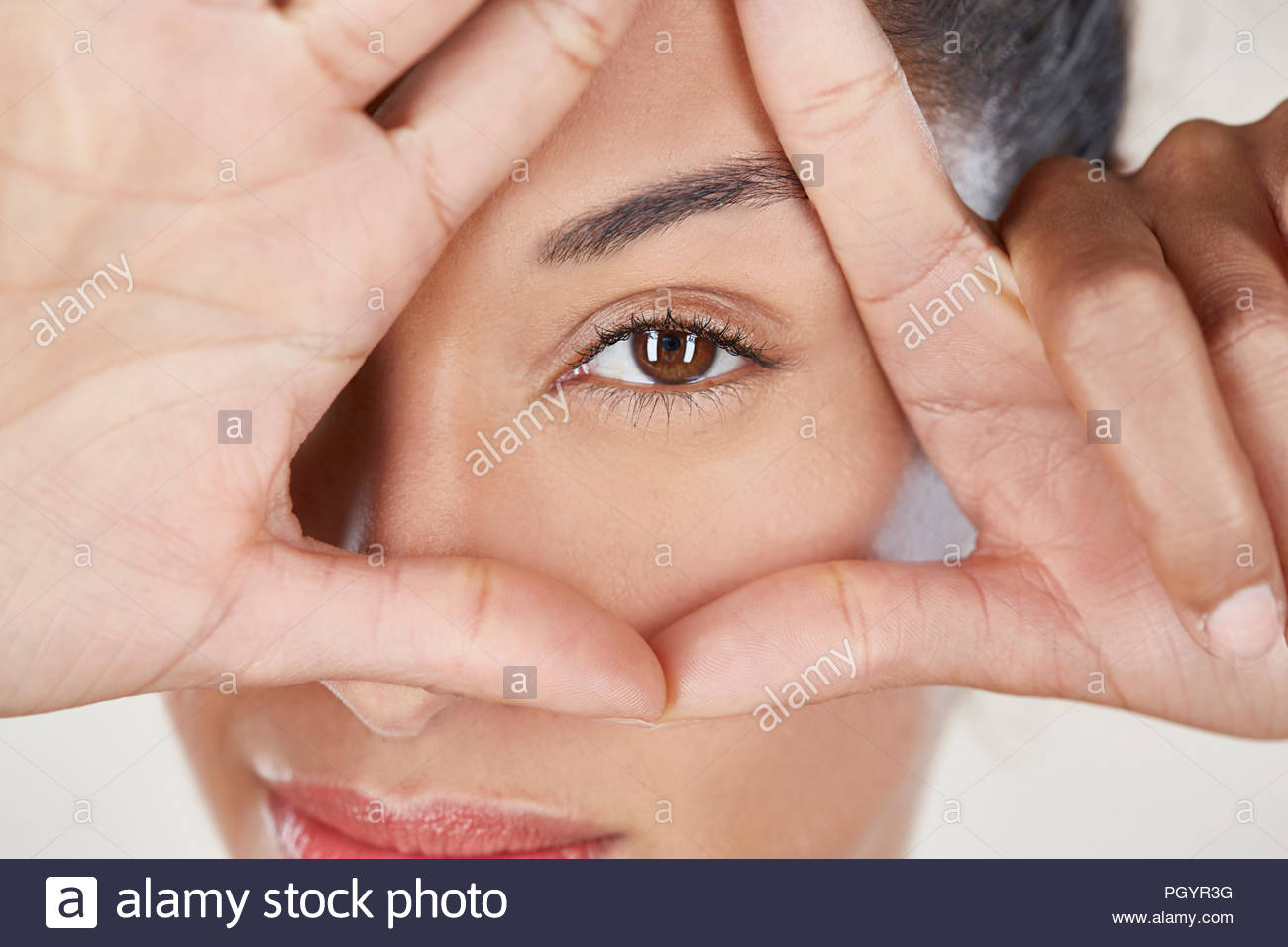 Portrait of woman looking through fingers. - Stock Image