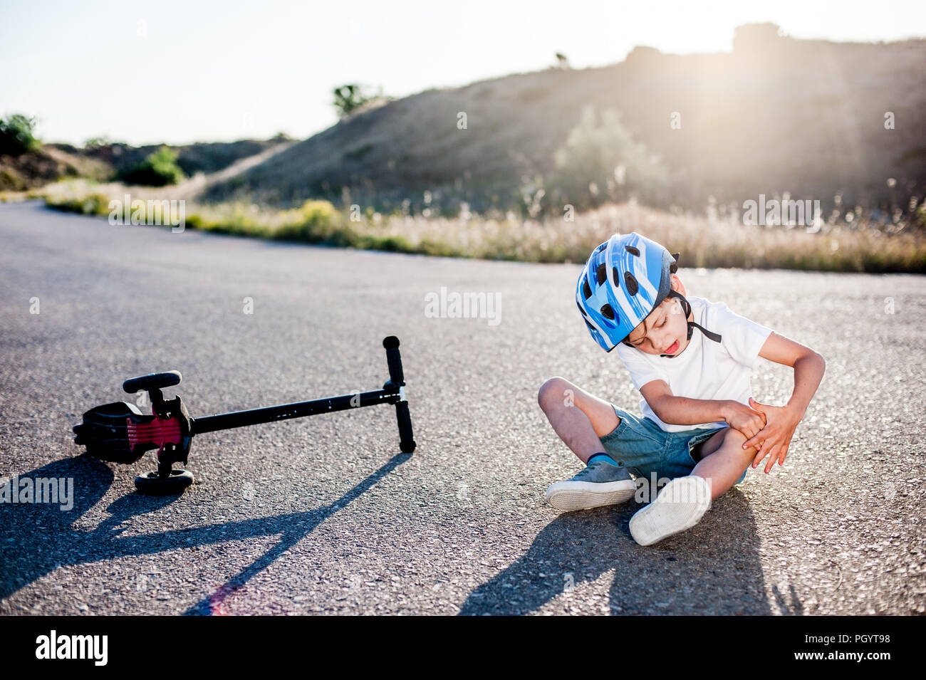 little sport kid holding his knee suffering from pain after road accident scooter - Stock Image