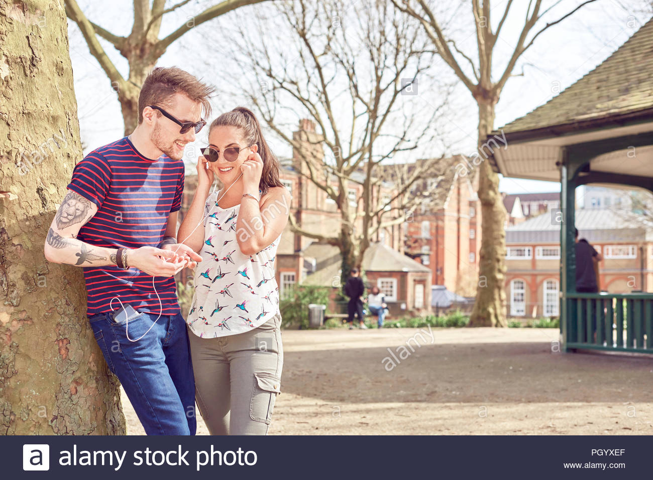 Teenage couple sharing music in park - Stock Image