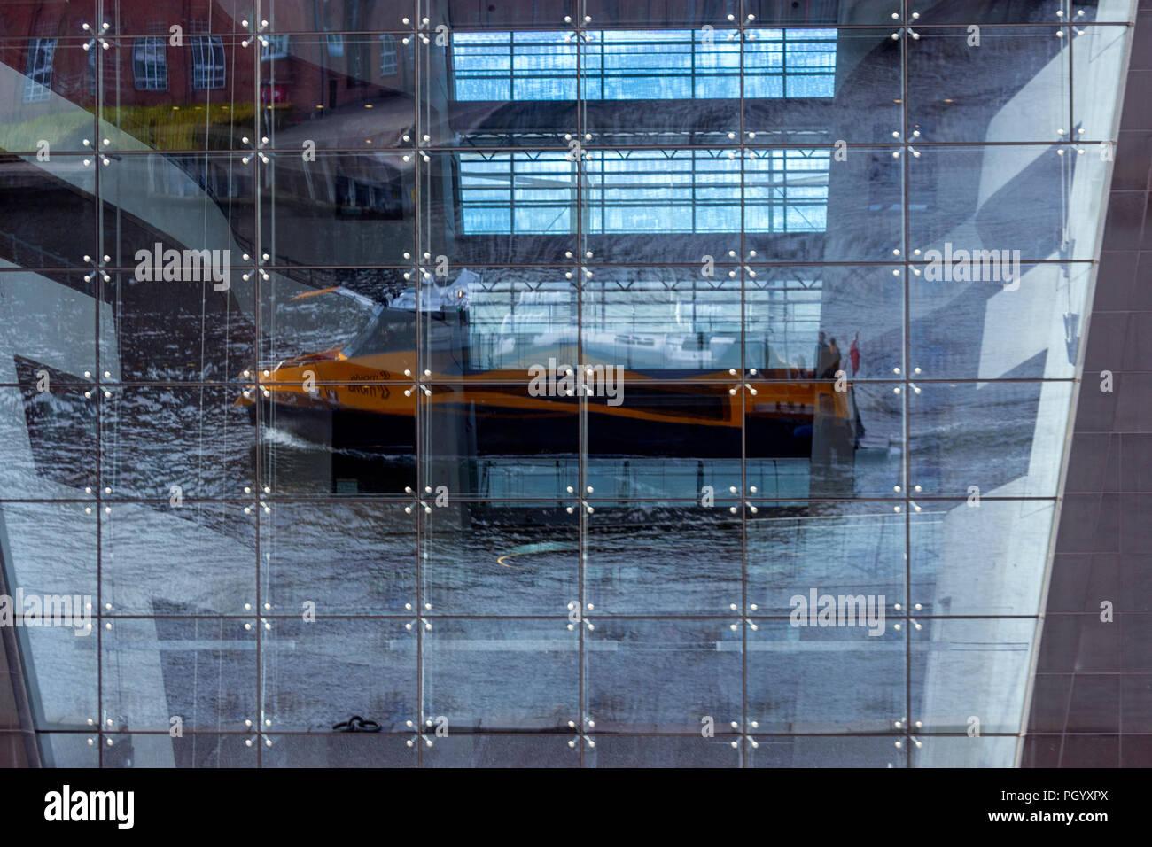 Bus boat reflections from the Royal Danish Library, The Black Diamond library, Designed by architects Schmidt Hammer Lassen, Copenhagen, Denmark. Stock Photo
