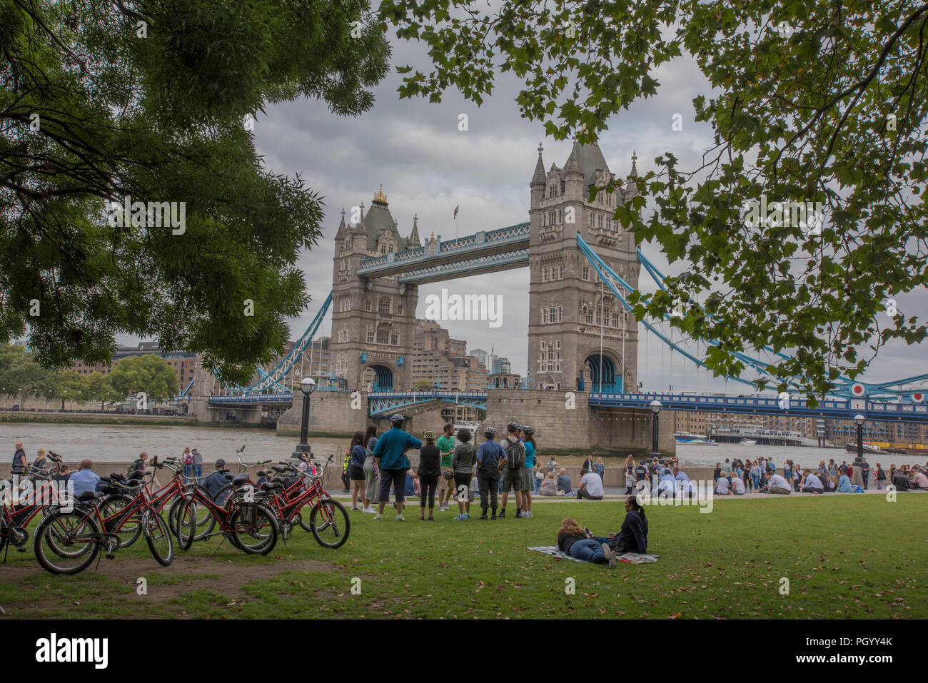 a group of oriental tourists on a guided cycle tour of london next to tower bridge at more london riverside. - Stock Image
