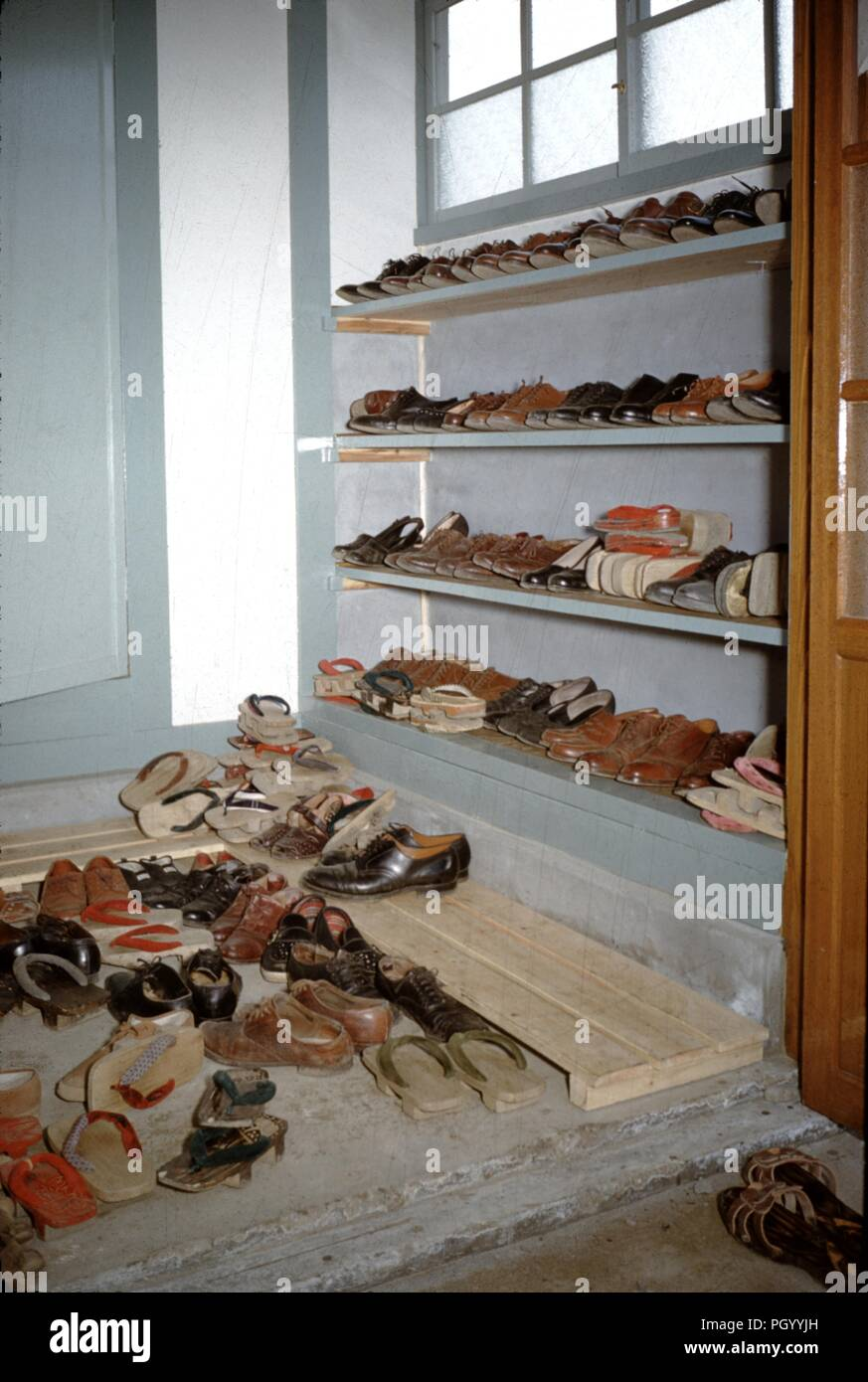 Traditional Japanese Genkan Or Entryway Used For The Ceremonial Removal Of Shoes Prior To Entering A Dwelling Stacked With Many Pairs Of Shoes Japan 1955 Stock Photo Alamy